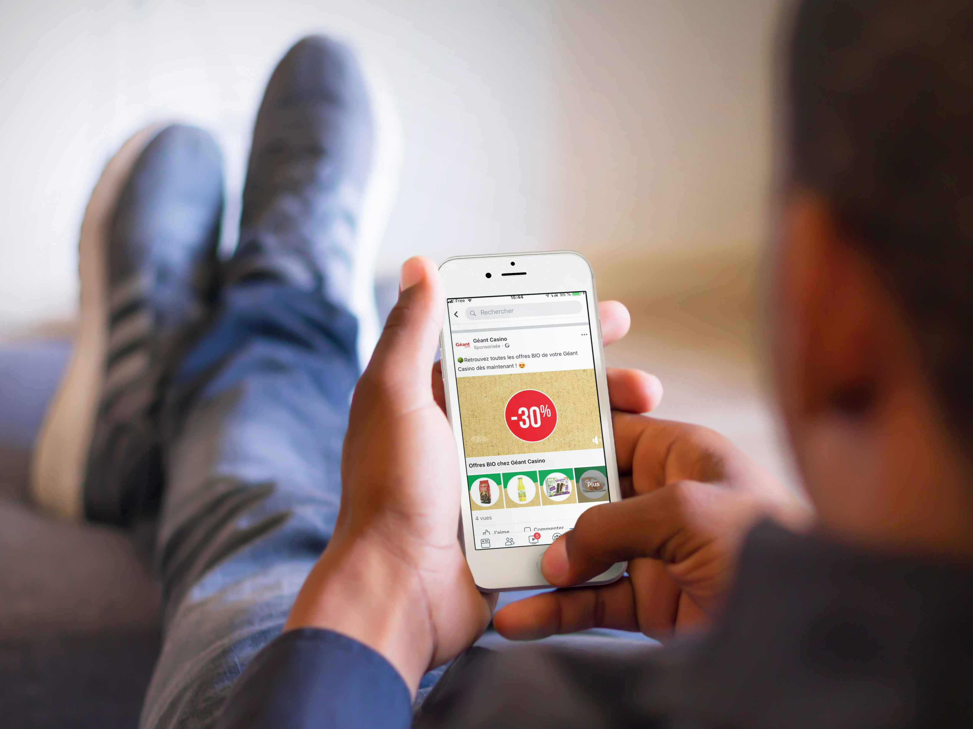 mockup-of-man-relaxing-with-his-feet-up-while-using-a-white-iphone-6 (1)-png